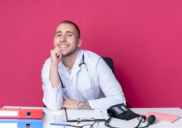 Glimlachende jonge mannelijke arts die medische robe en stethoscoopzitting bij bureau met werkhulpmiddelen draagt ?? die hand op kin zetten die op roze muur wordt geïsoleerd