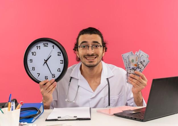 Glimlachende jonge mannelijke arts met een medische bril die een medische mantel draagt met een stethoscoop die aan het bureau zit