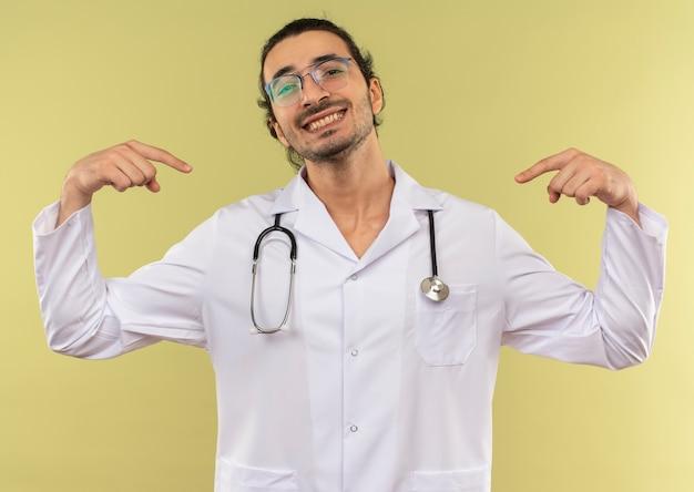 Glimlachende jonge mannelijke arts met optische bril die een wit gewaad met een stethoscoop draagt, wijst zichzelf op een groene achtergrond