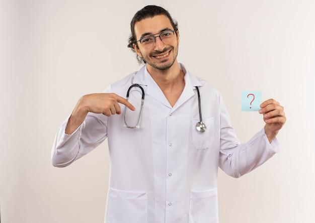 Glimlachende jonge mannelijke arts met optische bril die wit gewaad met stethoscoopholding draagt en wijst naar document vraagteken op geïsoleerde witte muur met exemplaarruimte