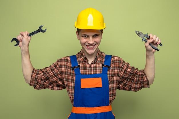 Glimlachende jonge mannelijke bouwer die een uniform draagt met een steeksleutel met een tang