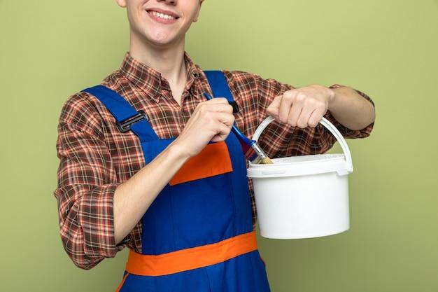 Glimlachende jonge mannelijke bouwer die een uniforme emmer met verfborstel draagt