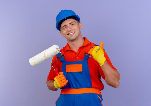 Glimlachende jonge mannelijke bouwer die eenvormig en veiligheidshelm in handschoenen draagt die verfroller zijn duim op paars houden