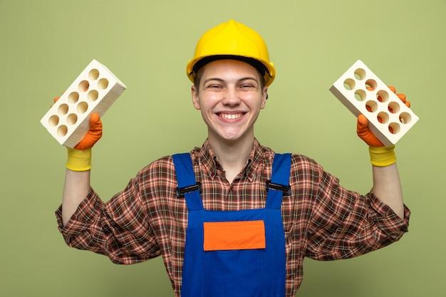 Glimlachende jonge mannelijke bouwer die uniform draagt met handschoenen die bakstenen vasthouden