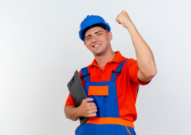Glimlachende jonge mannelijke bouwer die uniform en veiligheidshelm draagt ?? die klembord houdt en sterk gebaar op wit doet
