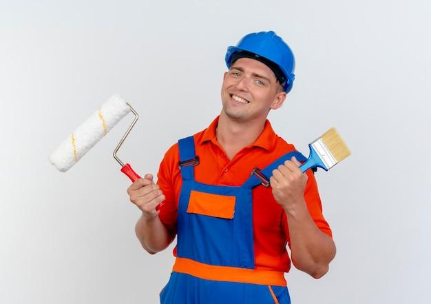 Glimlachende jonge mannelijke bouwer die uniform en veiligheidshelm dragen die verfroller met kwast op wit houden