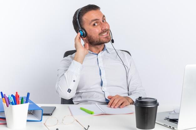 Glimlachende jonge mannelijke callcentermedewerker met een headset die aan tafel zit met kantoorhulpmiddelen geïsoleerd op een witte muur
