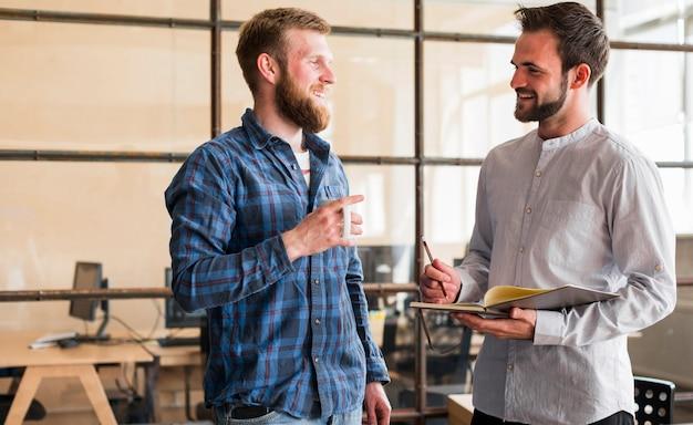 Glimlachende jonge mannelijke collega die elkaar kijkt