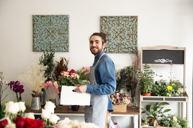 Glimlachende jonge mannelijke de holdingshydrangea hortensiainstallaties van de bloemist in het houten krat die aan camera kijken