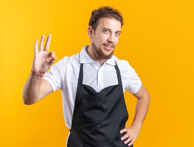 Glimlachende jonge mannelijke kapper die een uniform draagt met een goed gebaar dat de hand op de heup legt, geïsoleerd op gele achtergrond