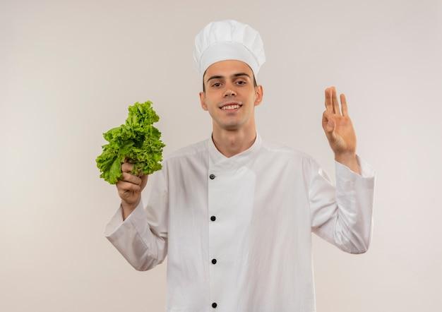 Glimlachende jonge mannelijke kok die de salade van de chef-kok eenvormige holding draagt die okgebaar toont