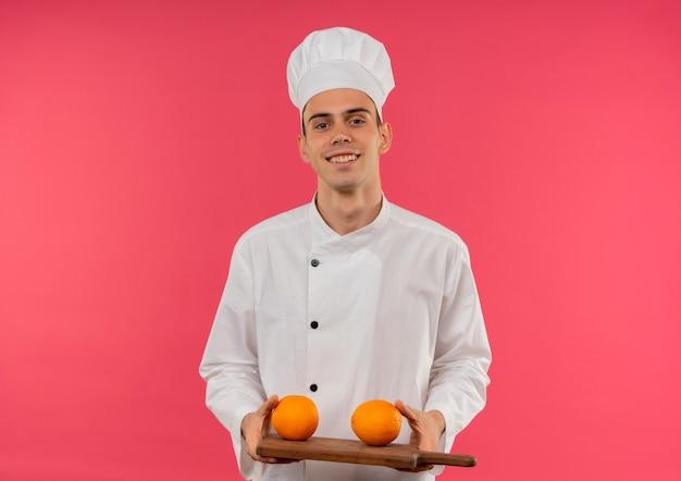 Glimlachende jonge mannelijke kok die de sinaasappel van de chef-kok eenvormige holding op scherpe raad met exemplaarruimte draagt