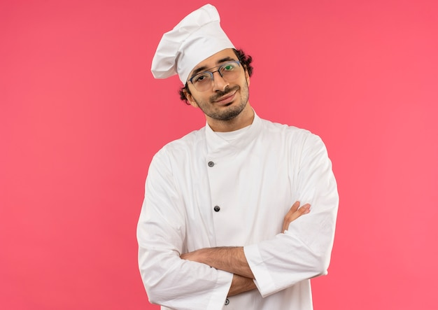 Glimlachende jonge mannelijke kok die eenvormige chef-kok en glazen draagt die handen op roze kruisen