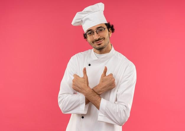 Glimlachende jonge mannelijke kok die eenvormige chef-kok en glazen draagt die handen zijn duimen kruisen die omhoog op roze muur worden geïsoleerd