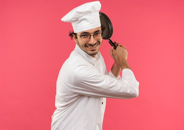 Glimlachende jonge mannelijke kok die eenvormige chef-kok en glazen draagt die koekenpan houden rond schouder die op roze muur wordt geïsoleerd
