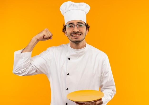 Glimlachende jonge mannelijke kok die eenvormige chef-kok en glazen draagt die plaat houdt en sterk gebaar doet dat op gele muur wordt geïsoleerd