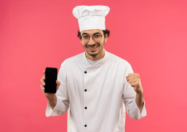 Glimlachende jonge mannelijke kok die eenvormige chef-kok en glazen draagt die telefoon houdt en ja gebaar toont dat op roze muur wordt geïsoleerd