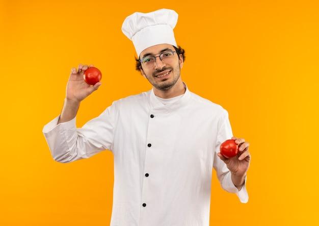 Glimlachende jonge mannelijke kok die eenvormige chef-kok en glazen draagt die tomaat houden die op gele muur wordt geïsoleerd