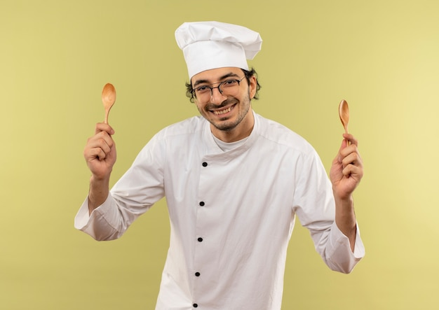 Glimlachende jonge mannelijke kok die eenvormige chef-kok en glazen dragen die lepels houden die op groene muur worden geïsoleerd