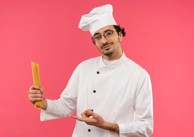 Glimlachende jonge mannelijke kok die eenvormige chef-kok en glazen houden en wijst naar spaghetti die op roze muur wordt geïsoleerd