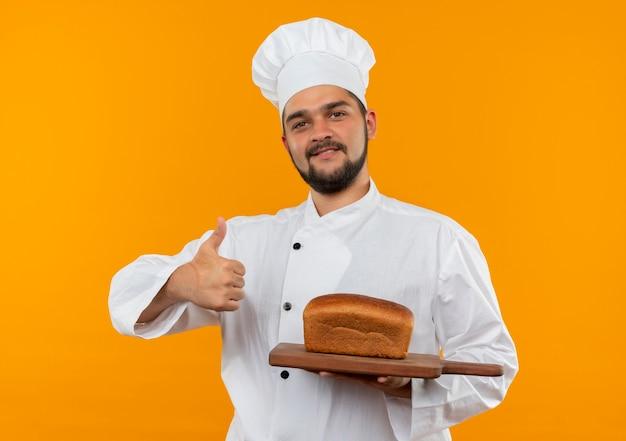 Glimlachende jonge mannelijke kok in chef-kok uniforme snijplank met brood erop houden en duim opdagen geïsoleerd op oranje ruimte
