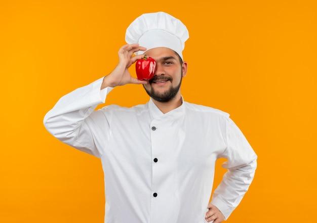 Glimlachende jonge mannelijke kok in eenvormige chef-kok die peper op oog en hand op taille zet die op oranje ruimte wordt geïsoleerd