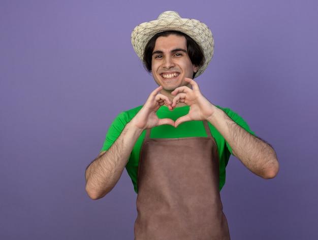 Glimlachende jonge mannelijke tuinman in eenvormig die het tuinieren hoed draagt die hartgebaar toont