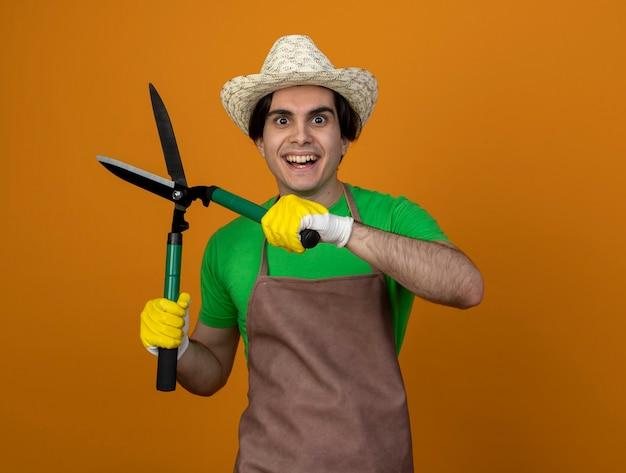 Glimlachende jonge mannelijke tuinman in uniform die tuinieren hoed met handschoenen draagt die tondeuse houden die op oranje muur wordt geïsoleerd