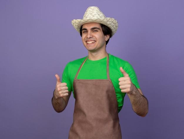 Glimlachende jonge mannelijke tuinman in uniform dragen tuinieren hoed duimen opdagen