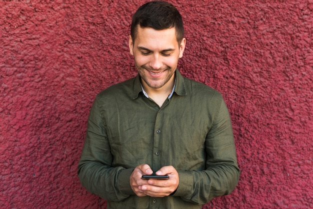 Glimlachende jonge mens bezig in sms bericht aan iemand