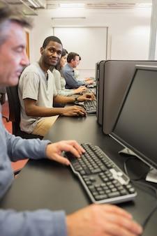 Glimlachende jonge mens bij computerklasse