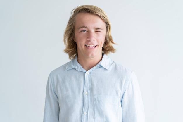 Glimlachende jonge mens die camera en het knipogen bekijkt