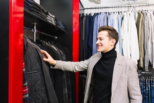 Glimlachende jonge mens die de kleren in het rek controleert