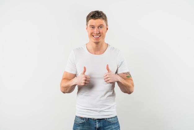 Glimlachende jonge mens die duim met twee handen tegen witte achtergrond toont