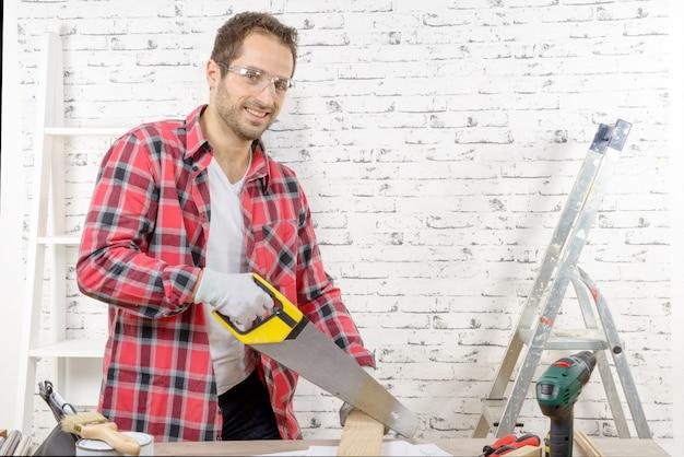 Glimlachende jonge mens die een raad met een handzaag snijdt