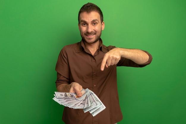 Glimlachende jonge mens die en op geld houdt richt die voorzijde bekijkt die op groene muur wordt geïsoleerd