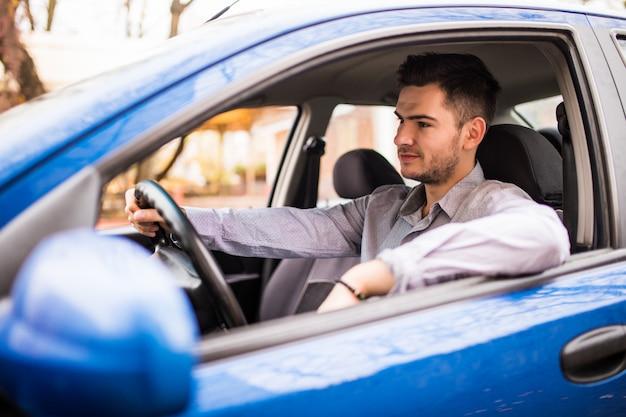 Glimlachende jonge mens die glazen dragen die achter het wiel van zijn auto het drijven door de stad zitten