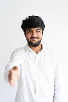 Glimlachende jonge mens die hand voor handdruk aanbieden en camera bekijken.