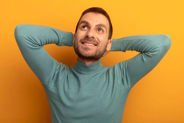 Glimlachende jonge mens die handen achter hoofd zet die omhoog geïsoleerd op oranje muur kijken