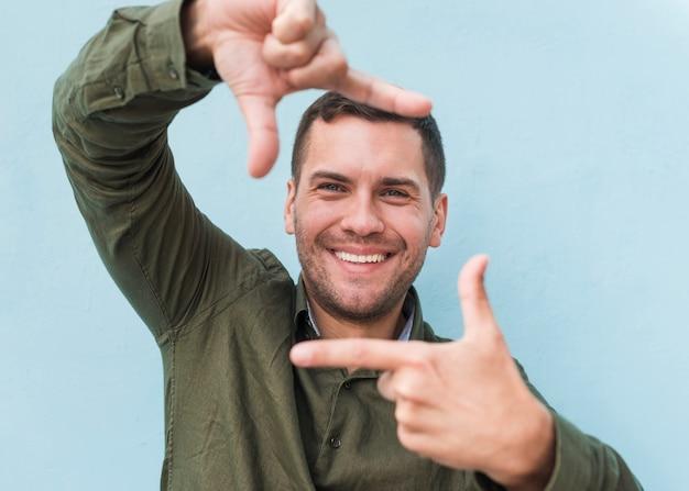Glimlachende jonge mens die handkader over blauwe achtergrond maakt