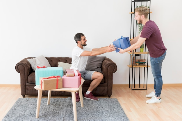 Glimlachende jonge mens die huidige doos geeft aan zijn vriend thuis
