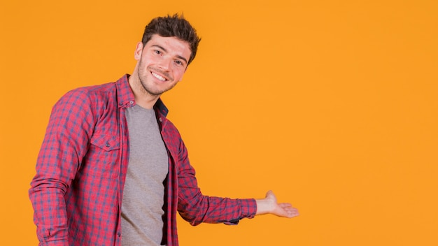 Glimlachende jonge mens die iets op een oranje achtergrond voorstelt