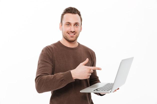 Glimlachende jonge mens die laptop computer het richten gebruikt.