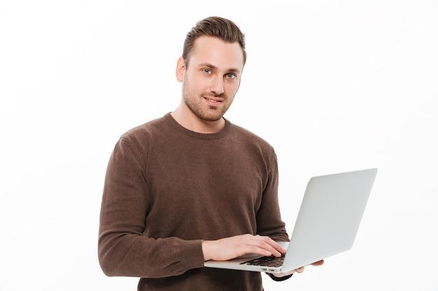 Glimlachende jonge mens die laptop computer met behulp van.