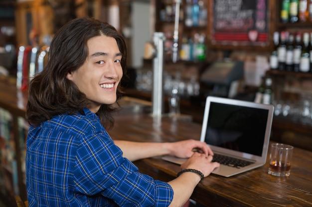 Glimlachende jonge mens die laptop met behulp van bij barteller