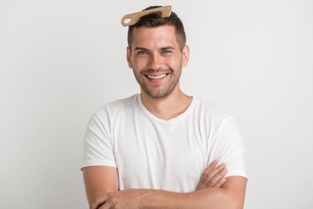 Glimlachende jonge mens die met kam in zijn haar camera bekijkt