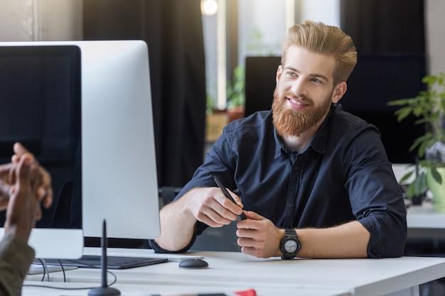Glimlachende jonge mens die met zijn collega spreekt
