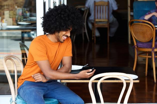 Glimlachende jonge mens die mobiele telefoon met behulp van bij koffie