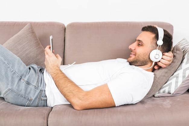 Glimlachende jonge mens die op bank het luisteren muziek op hoofdtelefoon door mobiele telefoon ligt