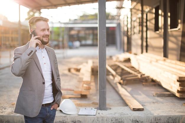 Glimlachende jonge mens die op cellphone bij bouwwerf spreekt